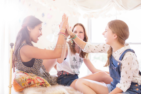Three teenage girls doing high five on bedの写真素材 [FYI02164480]