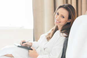 Portrait of smiling woman wearing white bathrobe with notebook in bedroomの写真素材 [FYI02164493]