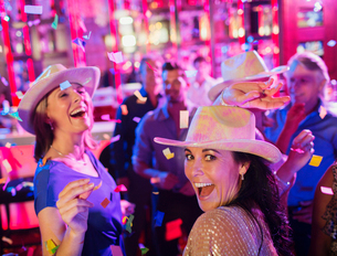 Confetti falling on women wearing cowboy hats laughing and dancing in nightclubの写真素材 [FYI02164527]