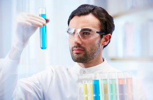 Man in laboratory looking at vial with blue fluidの写真素材 [FYI02164544]