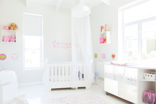 White crib with tulle canopy in pastel colored baby's roomの写真素材 [FYI02164599]