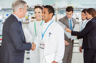 Scientist and businessman shaking hands in laboratoryの写真素材 [FYI02164608]