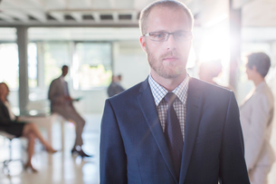 Portrait of serious businessman wearing glasses and suit standing in office, colleagues in backgrounの写真素材 [FYI02164614]