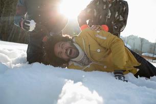 Friends enjoying snowball fightの写真素材 [FYI02164628]