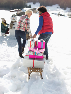 Couple pulling sled with Christmas gifts in snowの写真素材 [FYI02164634]
