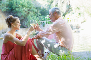 Couple toasting each other outdoorsの写真素材 [FYI02164642]