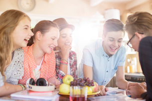 Group of smiling teenagers gathered around table in dining roomの写真素材 [FYI02164658]