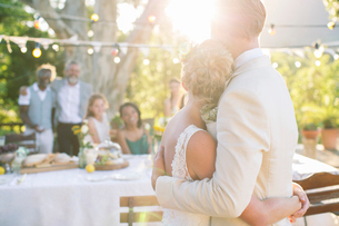 Young couple embracing in garden during wedding receptionの写真素材 [FYI02164669]