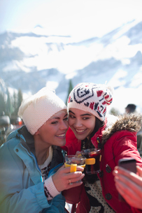 Smiling women in warm clothing drinking tea outdoorsの写真素材 [FYI02164700]