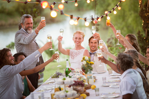 Young couple and their guests toasting with champagne during wedding reception in gardenの写真素材 [FYI02164756]