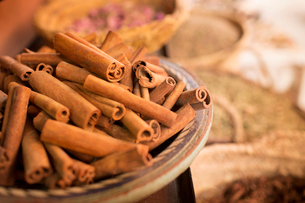 Cinnamon sticks on plate and other spices in background in spice marketの写真素材 [FYI02164817]