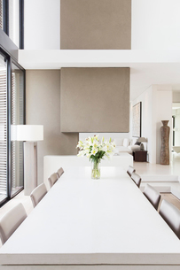 Modern white and beige dining room with large table and lilies in vaseの写真素材 [FYI02164828]