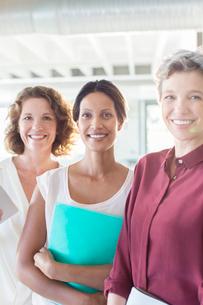 Portrait of three smiling businesswomen standing in officeの写真素材 [FYI02164832]