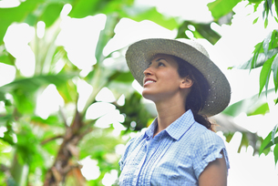 Smiling woman wearing straw hat looking at plants in sunny gardenの写真素材 [FYI02164849]