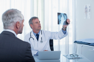 Doctor sitting at desk in office examining patient's x-rayの写真素材 [FYI02164887]