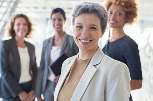Portrait of smiling mature businesswoman with office team in backgroundの写真素材 [FYI02164915]