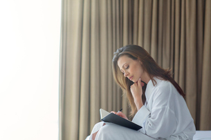 Pensive woman wearing white bathrobe writing in notepad in bedroomの写真素材 [FYI02164917]