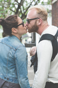 View of couple in sunglasses kissing and holding baby in city streetsの写真素材 [FYI02164961]