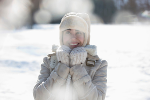 Woman in warm clothing smiling in snowの写真素材 [FYI02164979]