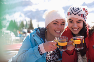 Portrait of smiling women in warm clothing drinking tea outdoorsの写真素材 [FYI02164983]