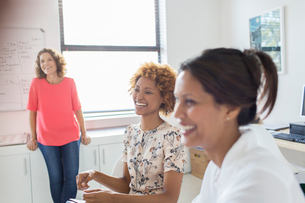 Three women laughing during meeting in officeの写真素材 [FYI02165006]