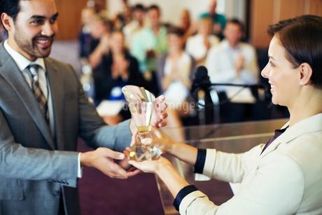 Businessman receiving award from smiling businesswomanの写真素材 [FYI02165031]