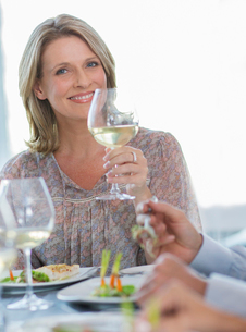 Portrait of smiling woman holding glass of white wine at restaurant tableの写真素材 [FYI02165044]