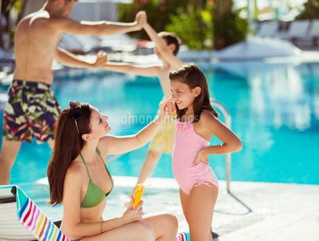 Mother applying suntan lotion on daughter's face by swimming poolの写真素材 [FYI02165047]