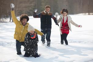 Friends enjoying snowball fightの写真素材 [FYI02165054]