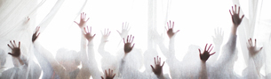 Silhouette of people raising hands behind transparent curtainの写真素材 [FYI02165062]