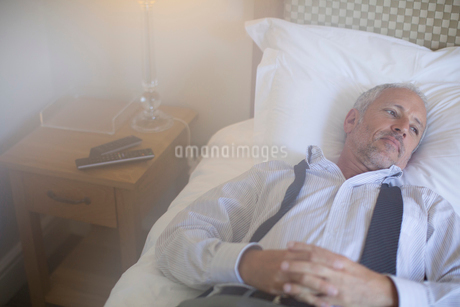 Businessman relaxing on bed in hotel roomの写真素材 [FYI02165118]