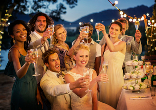 Wedding guests toasting with champagne during wedding reception in gardenの写真素材 [FYI02165142]