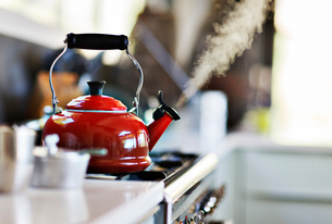 Red old fashion kettle on cooker with steam coming outの写真素材 [FYI02165151]
