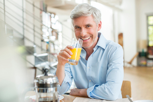Older man drinking orange juice at breakfast tableの写真素材 [FYI02165195]