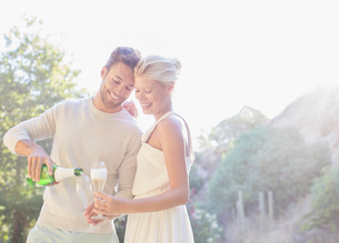 Couple drinking champagne outdoorsの写真素材 [FYI02165205]