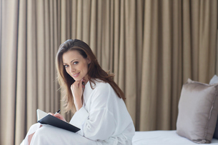 Portrait of woman wearing bathrobe with notepad in bedroomの写真素材 [FYI02165234]