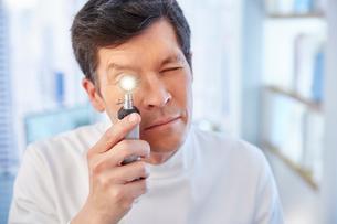 Man looking through illuminated speculum in laboratoryの写真素材 [FYI02165327]