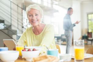 Older woman using digital tablet at breakfast tableの写真素材 [FYI02165365]