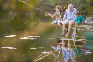 Grandfather and grandsons fishing and playing with toy sailboat at lakeの写真素材 [FYI02165406]