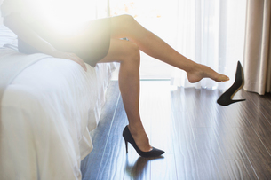 Businesswoman kicking off her shoes in hotel roomの写真素材 [FYI02165411]
