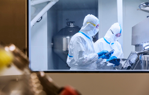 Scientists in clean suits using digital tablets in experiment in laboratoryの写真素材 [FYI02165417]