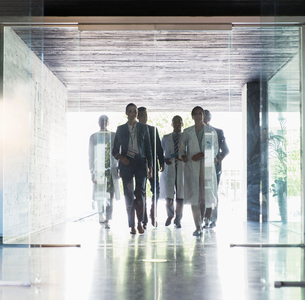 Scientists and business people approaching glass doorsの写真素材 [FYI02165430]