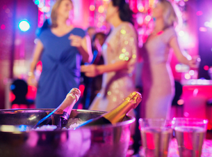 Champagne bottles in ice bucket and champagne flutes in nightclub, women dancing in backgroundの写真素材 [FYI02165468]