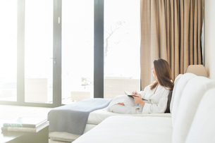 Woman wearing white bathrobe reclining on sofa in living room and looking through windowの写真素材 [FYI02165483]