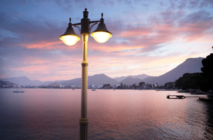 View of illuminated street light with bay and mountains in backgroundの写真素材 [FYI02165492]