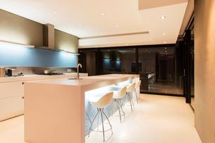 Modern white kitchen with kitchen island and stools illuminated at nightの写真素材 [FYI02165499]