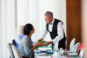 Smiling waiter serving salad to woman sitting at table in restaurantの写真素材 [FYI02165536]