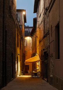 View of cafe table in town alley illuminated at duskの写真素材 [FYI02165539]