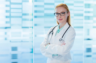 Portrait of smiling female doctor wearing glasses and lab coat standing with arms crossedの写真素材 [FYI02165542]