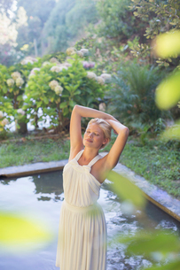 Woman standing by pool outdoorsの写真素材 [FYI02165546]